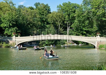 NEW YORK - SEPTEMBER 06: People Enjoying Sunny Day in Row Boats in front of Footbridge on Lake in Central Park, New York City, New York, USA. September 06 2015.