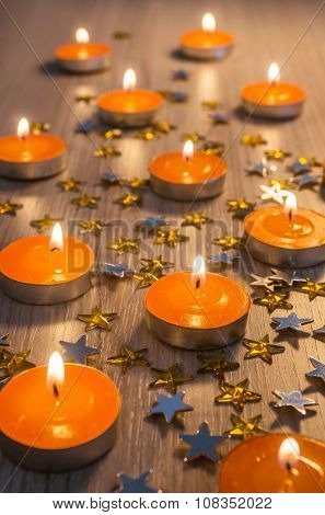 Christmas decoration with group of orange candles and yellow shining stars