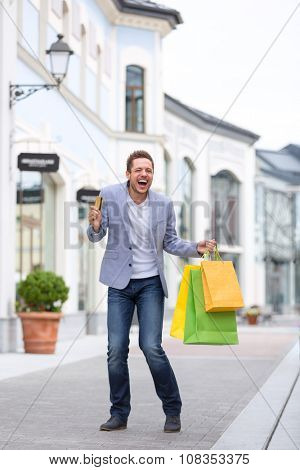 Expressive man with bags in shopping outlets