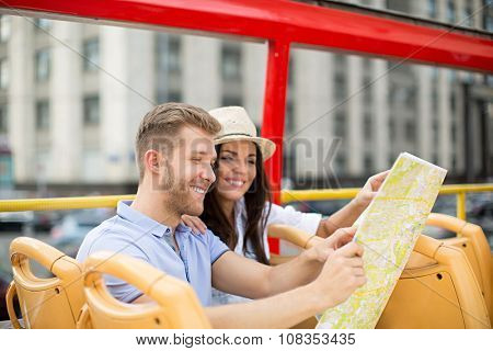 Young couple with a map of the tour bus