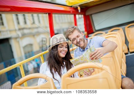 Smiling couple with a map of the tour bus