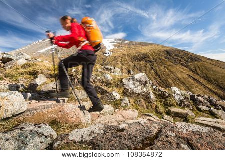 Pretty, young female hiker going uphill (motion blur technique used to convey movement of the hiker)
