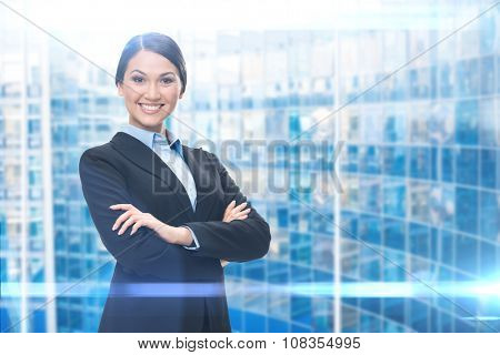 Portrait of female executive with hands crossed, blue background. Concept of leadership and success