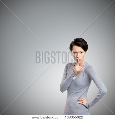 Pretty woman shows shush gesture, isolated on grey background