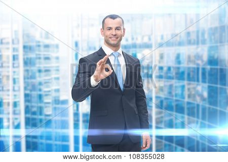 Portrait of businessman ok gesturing, modern background. Concept of leadership and success