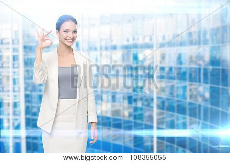 Portrait of business woman ok gesturing, modern blue background. Concept of leadership and success