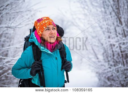 Young backpacking woman enjoy nature in beautiful winter forest