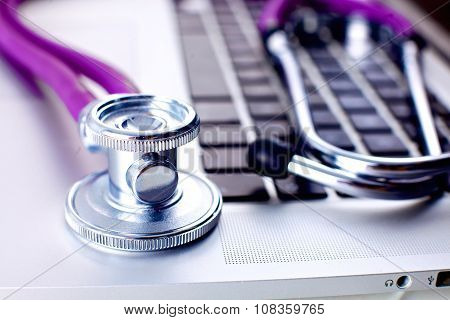 Medical stethoscope lying on a computer keyboard, a cup of coffee