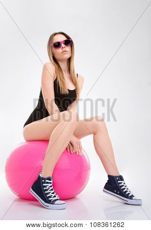 Beautiful attractive confident relaxed young woman in black leotard and pink sunglasses posing on pink fitball
