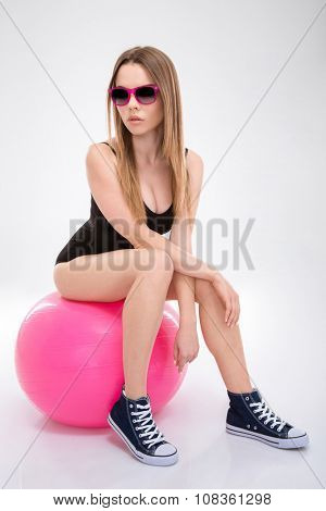 Modern style pretty young dancer in black leotard and pink sunglasses posing on pink fitball