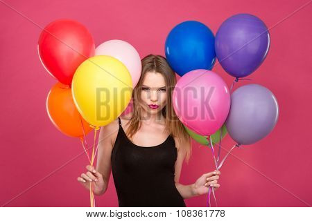 Attractive flirty concentrated young woman with colorful balloons thinking and planning surprise