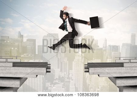 Energetic business man jumping over a bridge with gap concept