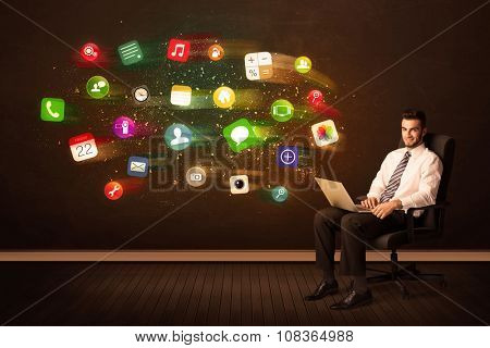 Business man sitting in office chair with laptop and colorful app icons concept on background
