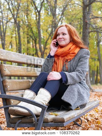 redhead girl talk on phone and sitting on a bench in city park, fall season