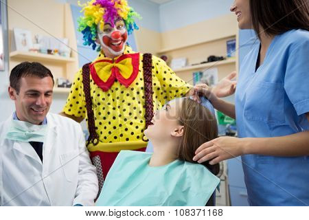 Funny clown in dental office make laugh young girl