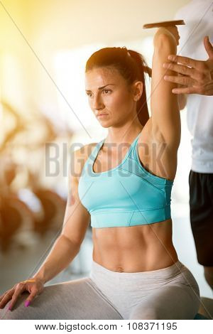 Trainer correcting woman with lifting dumbbells