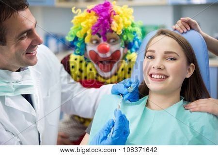 Pretty girl in dental clinic with dentist and silly clown in background