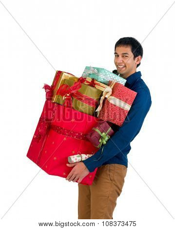 Happy young man holding too many Christmas presents