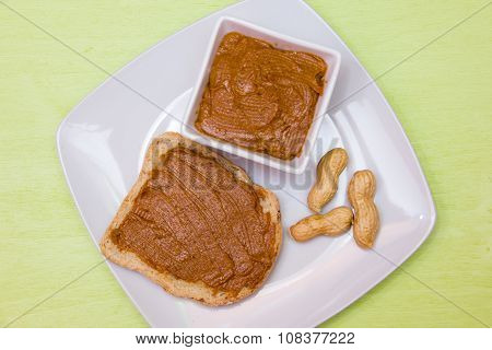 Slice of bread with peanut butter on green top