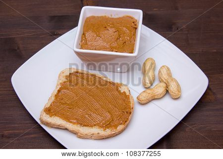 Slice of bread with peanut butter on wood