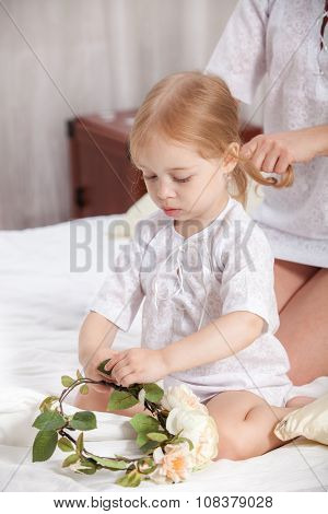 mother combs the little daughter in a bed