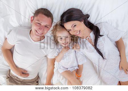 Happy family lying on a bed together in the bedroom