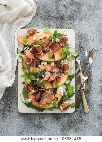 Prosciutto, melon, fig and soft cheese salad on a white serving board over grunge background