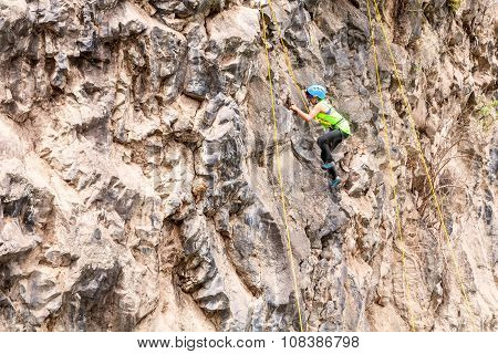 Young Girl Climbing A Vertical Rock Wall