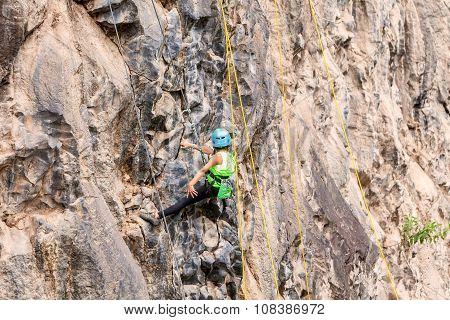 Ambitious Girl Climbing A Rock Wall