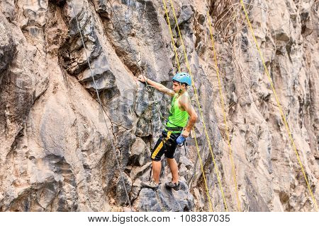 Young Man Climbing A Vertical Stone Wall