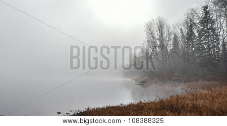 Dense heavy fog with diffused bright sunlight on a bay.