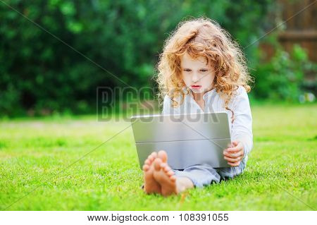 Little Girl Sitting On Grass And Playing Tablet Pc, Toning Photo.