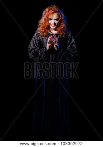Young witch girl isolated on black