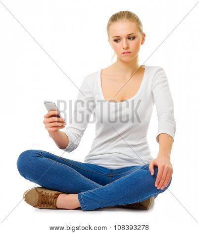 Young girl in jeans with mobile phone isolated
