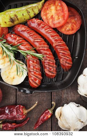 Grilled sausages and vegetables in grilling pan