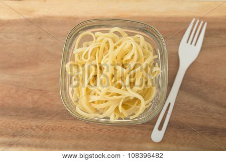 a small portion of linguini pasta in a glass storage container