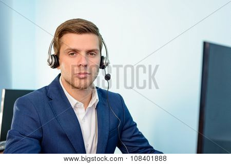 Young Customer Support Phone Operator with Headset at his Working Place in the Office.