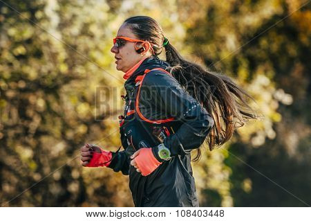 young woman athlete with watch and headphones running through woods