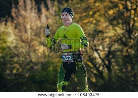 middle-aged man athlete running autumn forest in compression clothing