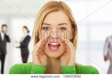 Beautiful young woman whispers gossip.