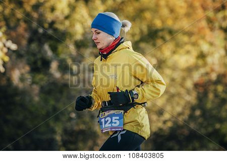young woman runner running in autumn forest