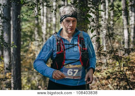 athlete middle-aged man runs through forest