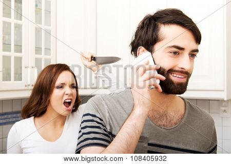 Young rage woman hitting her talking partner with frying pan.