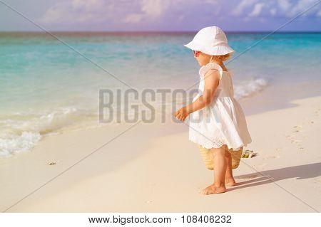 cute little girl with bag walking on beach