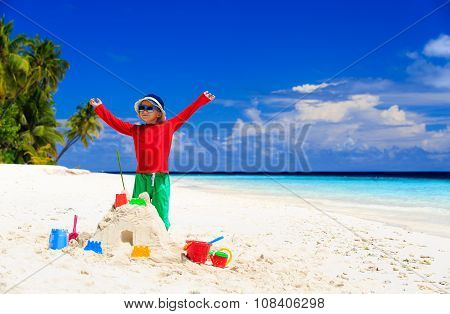 happy little boy with built sandcastle on beach
