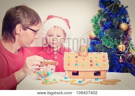 father and son decorating gingerbread house