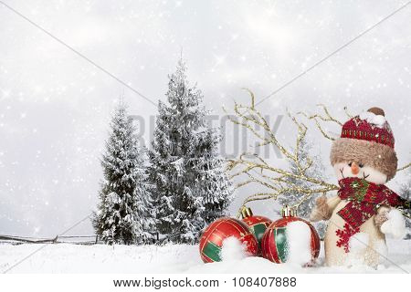 Snowman and red Christmas decorations in the snow, snow cowered pine trees in the background