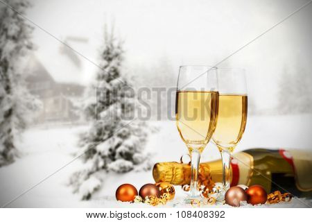 Glasses with champagne and Christmas decorations, snow cowered pine trees in the background