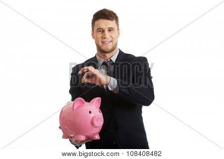 Young businessman putting a coin to piggybank.