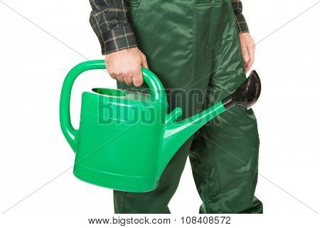 Gardener's hand holding green watering can.